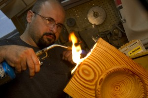Michael Pietras applying charred texture to historic turning